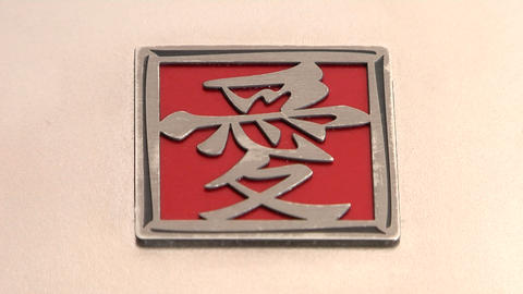 A red and silver square with Asian characters lies on a... Stock Video Footage