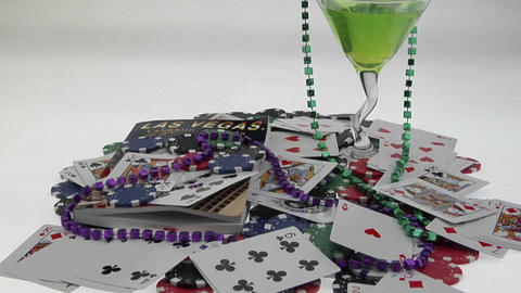 Pan-up to a pile of playing cards, poker chips, a drink,... Stock Video Footage
