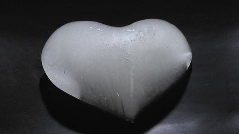 An ice heart melts on a dark surface Stock Video Footage