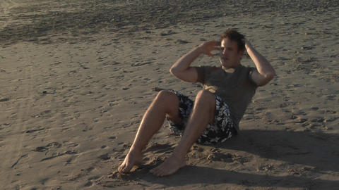 A man does sit-ups on a sandy beach Stock Video Footage