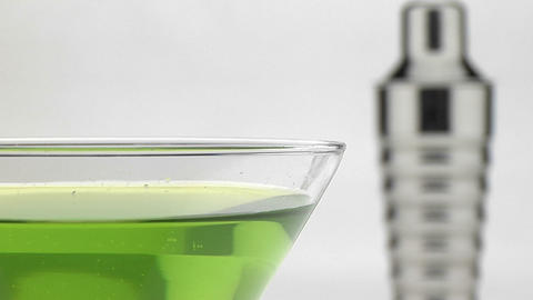 A silver martini shaker sits behind a glass with green... Stock Video Footage