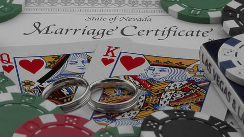 Wedding rings and a marriage certificate sit atop playing... Stock Video Footage