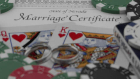 Wedding rings and a marriage certificate sit atop playing cards and poker chips Footage
