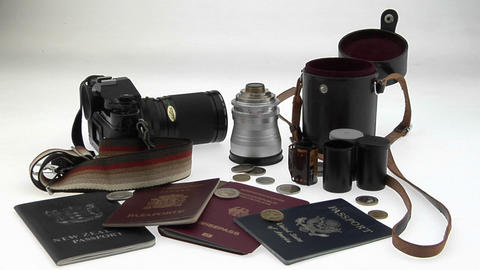 Travel and photography equipment sit on a white surface Stock Video Footage