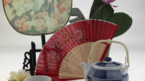 A Japanese tea set is framed by a Japanese-style fan and... Stock Video Footage