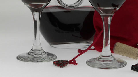 glasses filled with red wine and surrounded by a half-full carafe and red velvet bag are displayed o Footage