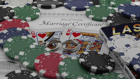 A marriage certificate sits nestled under playing cards and poker chips Footage