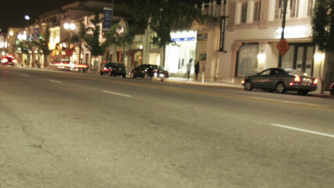 Cars speed down a city street Stock Video Footage