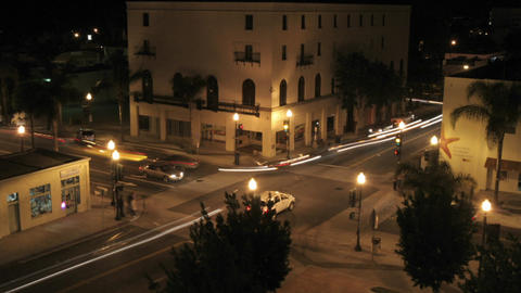 Traffic speeds through a city intersection at night Stock Video Footage