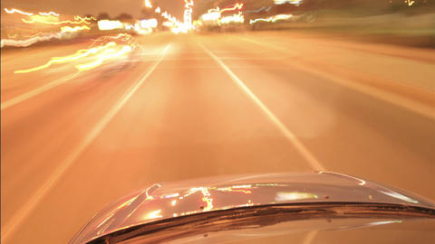 A car speeds along city streets at night Stock Video Footage