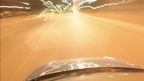 A car speeds along city streets at night Footage