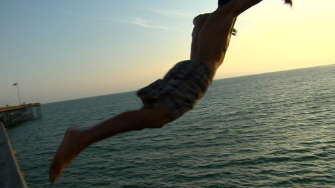 A young man climbs onto the rail of a pier and plunges... Stock Video Footage