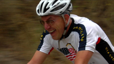 A bicyclist pedals hard in a rural road race Stock Video Footage