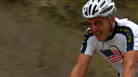A bicyclist pedals hard in a rural road race Footage