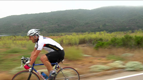 A bicyclist smiles as he peddles along a highway in a... Stock Video Footage