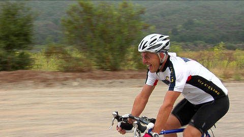 A bicyclist smiles as he peddles along a highway in a rural area Footage