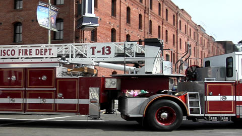 A hook-and-ladder fire truck turns a corner in an urban area Footage