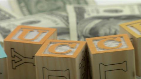 "Arranged wood blocks spell out the word success"" on top of a pile of paper currency Live Action"