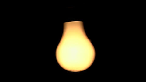Three bare illuminated light bulbs swing against a black background Footage