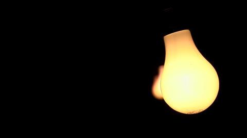 Three bare illuminated light bulbs swing against a black... Stock Video Footage