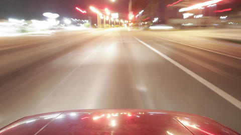 A shiny car travels on city streets at night Stock Video Footage
