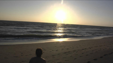 A man stands on the beach with his surfboard Stock Video Footage