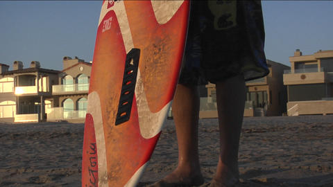 A man grabs his surfboard and runs towards the ocean Stock Video Footage