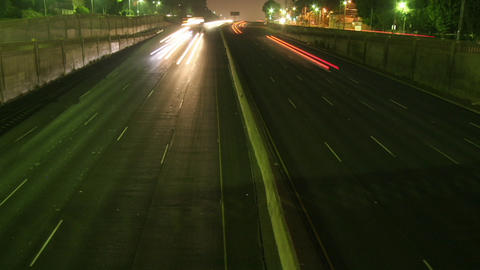 Traffic drives along a freeway at night Stock Video Footage