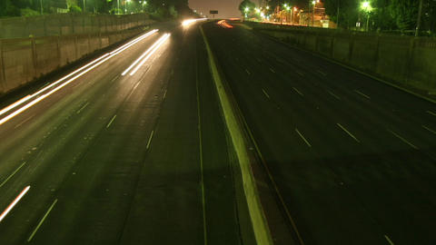 Traffic drives along a freeway at night Footage