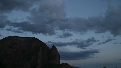Clouds rolls across the sky above a rock formation Footage
