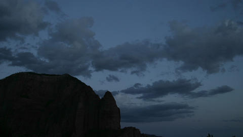 Clouds rolls across the sky above a rock formation Stock Video Footage