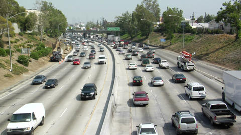 Heavy traffic moves in opposite directions along a four lane highway Footage