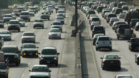 Traffic moves slowly on a busy freeway Stock Video Footage