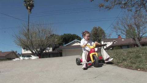 A girl loses her footing on a plastic tricycle and rolls... Stock Video Footage