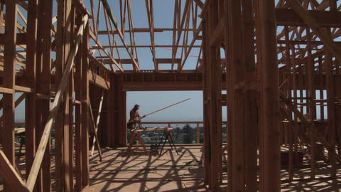 A contractor carries a piece of wood through the open... Stock Video Footage