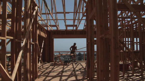 A contractor carries a piece of wood through the open frame of a home Footage