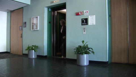 A businesswoman walks out of an elevator pulling a crate... Stock Video Footage