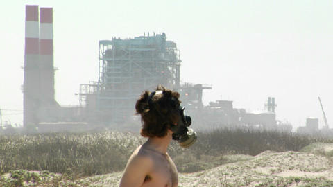 A man in a gas mask stands in front of a power plant Footage