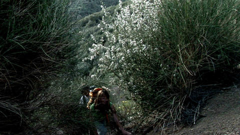 A woman and man hike up a hillside Stock Video Footage
