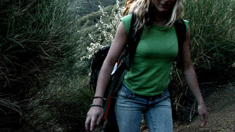A woman and man hike up a hillside Footage
