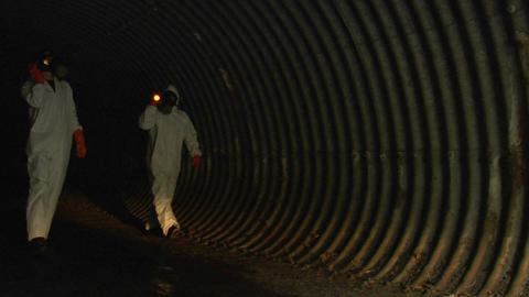 individuals wearing hazmat suits use flashlights to inspect a dark tunnel Footage