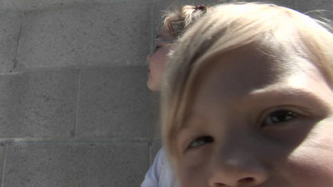 A girl gets very close to the camera while another sits... Stock Video Footage