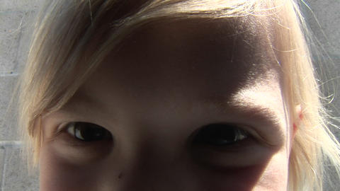 A girl gets very close to the camera while another sits next to a wall Footage
