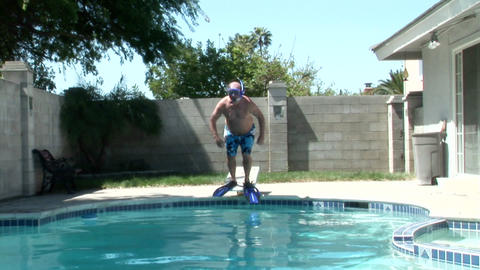A man wearing fins and a snorkel jumps off of a diving board into a pool Footage