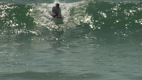 A bodyboarder in a hazmat suit rides a wave Stock Video Footage