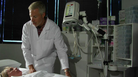 A man in a lab coat talks to a patient about a procedure Footage