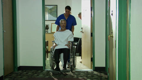 A nurse wheels a patient down a hallway Stock Video Footage