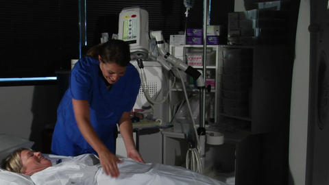 A nurse adjusts a patient by a hospital machine Footage