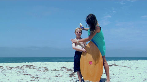 A woman rubs sunscreen on a boy at the beach Stock Video Footage