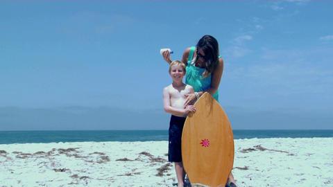 A woman rubs sunscreen on a boy at the beach Footage